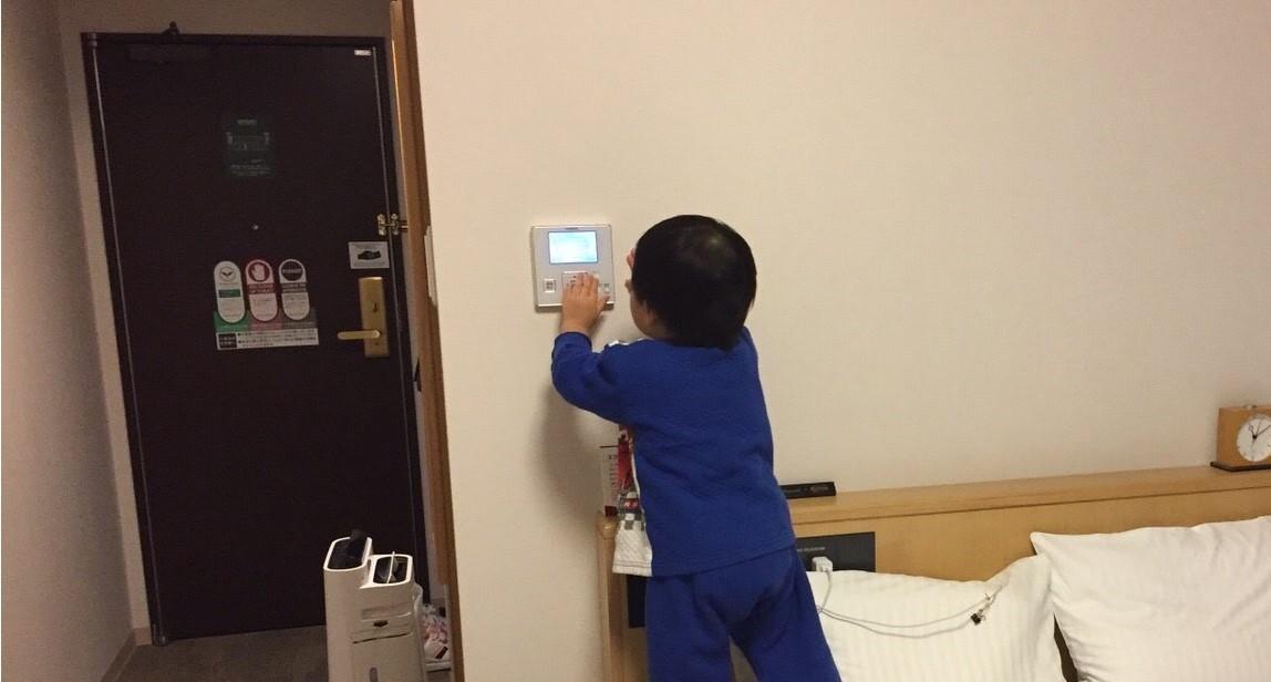 リッチモンドホテル浜松の部屋のエアコンのスイッチを触る息子の写真