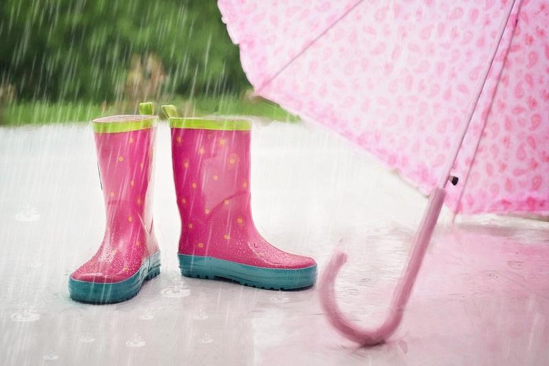 雨に打たれる子供用のピンクの傘と長ぐづの写真